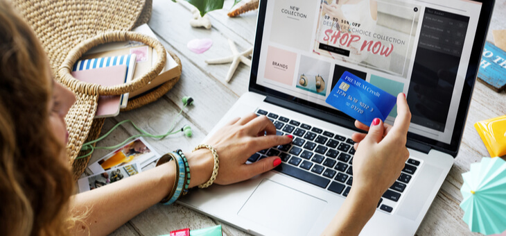 woman holding credit card while shopping at laptop