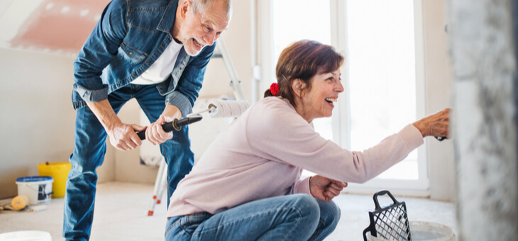 older couple laughing while painting walls