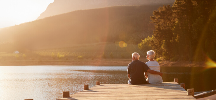 retired couple sitting on jetty at lake