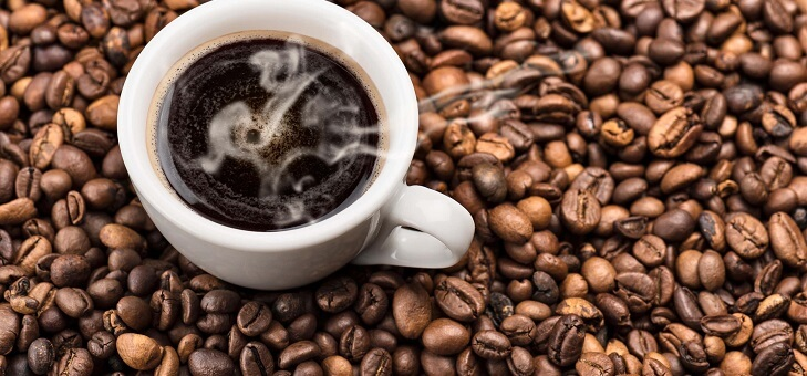steaming cup of black coffee sitting on bed of coffee beans