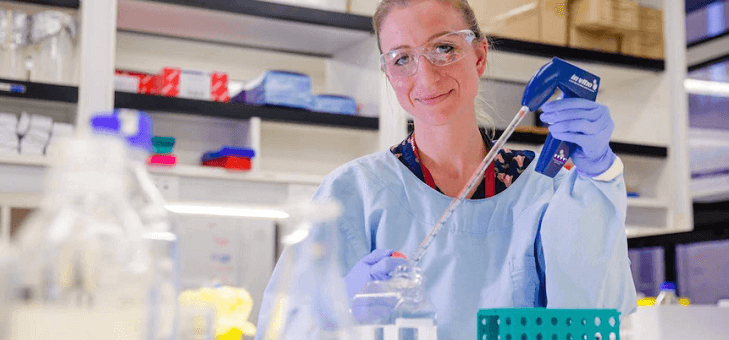 female scientist in protective gear with dropper and beaker