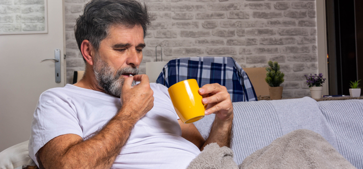 man on couch under blanket taking pill with drink
