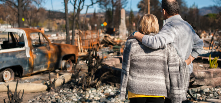 couple looking at burnt remains of their home