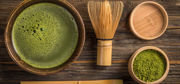 aerial view of cup of matcha tea and bamboo stirring utensils