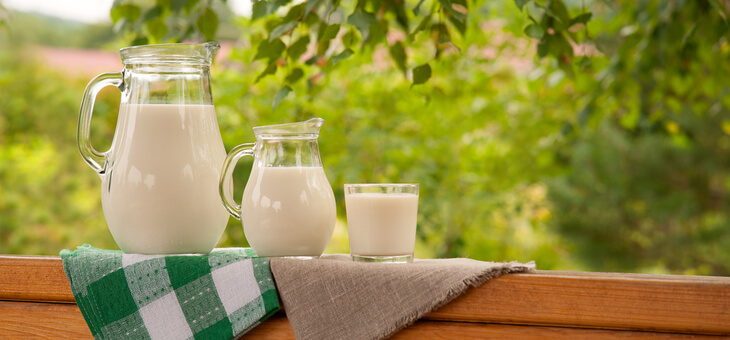 two jugs and a glass of milk sitting on fence