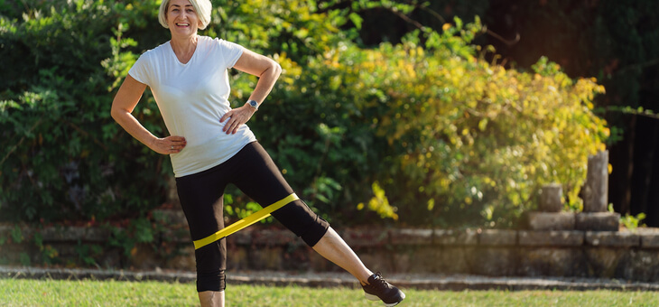 woman stretching legs with resistance band