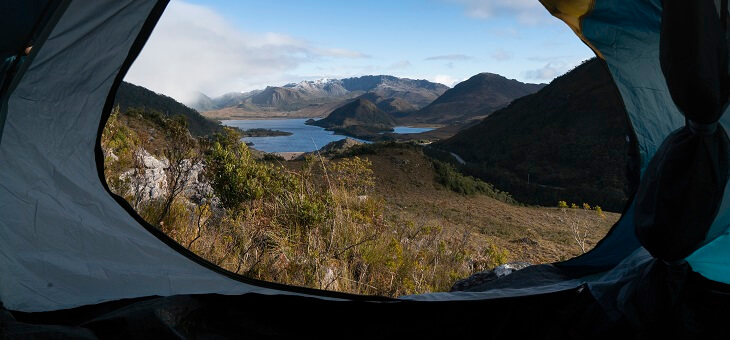 view of lake and mountains through open tent flap