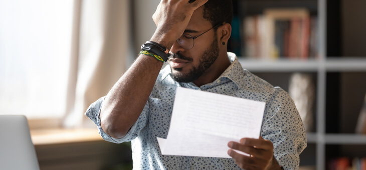 stressed man at laptop holding palm to forehead