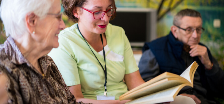 woman reading a book to elderly woman in care home
